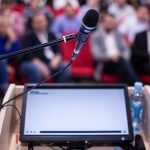 Podium presentation with laptop and microphone